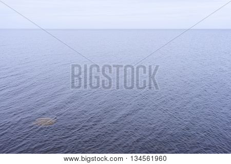 Swell on the Baltic Sea to the horizon lines and circles of stones underwater