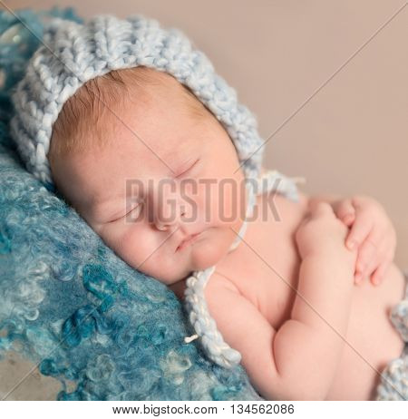 sweet newborn in knitted hat sleeping on woolen blanket close up