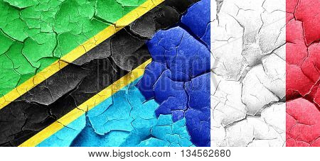 Tanzanian flag with France flag on a grunge cracked wall