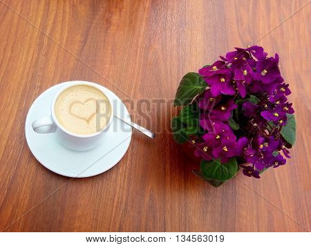 Cup of coffee and pretty purple flowers on the table