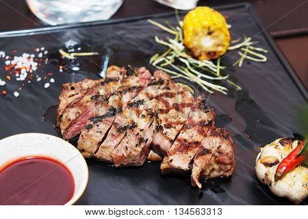 barbeque meat composition on a black background with tomato sauce, corn, rosemary and pepper. Appetizing meat roasted BBQ grill