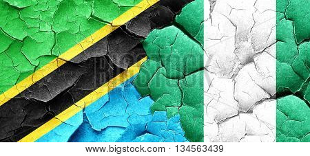 Tanzanian flag with Nigeria flag on a grunge cracked wall