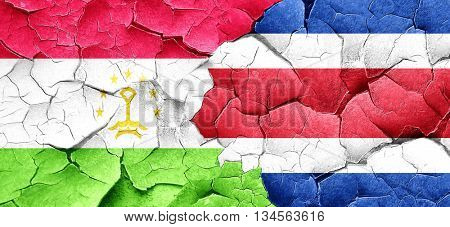 Tajikistan flag with Costa Rica flag on a grunge cracked wall