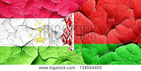 Tajikistan flag with Belarus flag on a grunge cracked wall