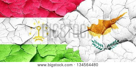 Tajikistan flag with Cyprus flag on a grunge cracked wall