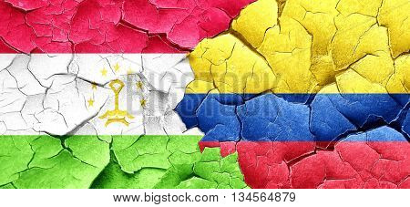 Tajikistan flag with Colombia flag on a grunge cracked wall