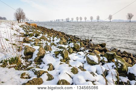 Wide Dutch river in the winter season. A layer of white snow has fallen on the stones on the bank of the river.