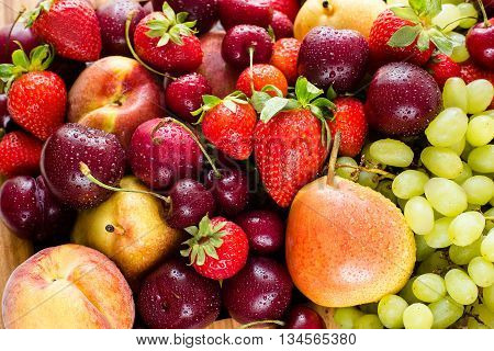 Fresh mixed fruits and berries.Fruits, berries background.Healthy eating, dieting.Love fruits, clean eating. Grape, lemons, apricots, peaches and pears and strawberies and cherry.colorful background