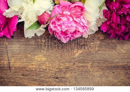 Peony background. Fuchsia, pink and white peonies on wooden table with place for text. Spring flower peony. Happy Mothers Day. Mother's Day greetings card. Mothers Day gift. Valentines Day.Copy space.