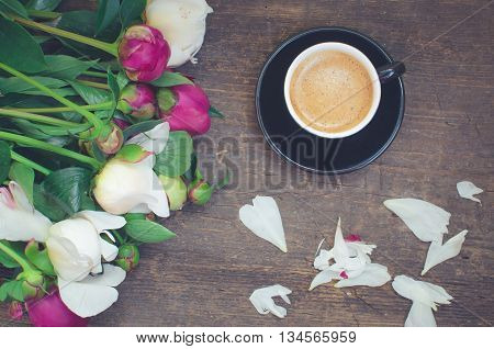 Coffee break. Coffee and flowers peony. A cup of coffee and Peonies on a wooden table. Breakfast on Mothers day, Valentines Day or Womens day. Spring or summer background. Top view. Toned image.