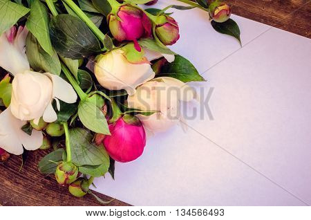 Peony background. Fuchsia, pink and white peonies on old wooden table with an empty sheet of paper for text. Happy Mothers Day. Mother's Day greetings card. Valentines Day. Copy space. Toned image.