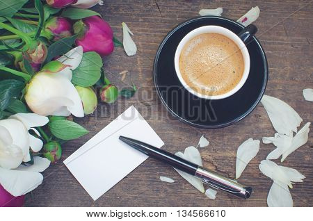 A cup of coffee and flowers Peonies on a table with an empty card for text and pen. Breakfast on Mothers day, Valentines Day or Womens day. Writing greetings card. Copy space. Top view. Toned image.