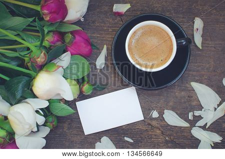 A cup of coffee and flowers Peonies on a wooden table with an empty card for text. Breakfast on Mothers day, Valentines Day or Womens day. Spring Peony background. Copy space. Top view. Toned image.