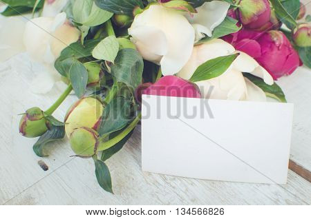 Peony background. Fuchsia, pink and white peonies on white wooden table with an empty card for text. Happy Mothers Day. Mother's Day greetings card. Valentines Day. Copy space. Toned image.