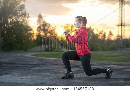 Fit woman in sportswear doing frontal lunges (squats). Fitness workout sport outdoors concept.