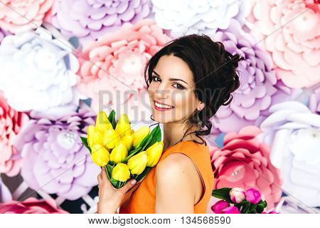 Beautiful young woman in yellow dress posing by the background of paper flowers. Beauty fashion. Haircare. Cosmetics.