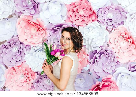 Beautiful yong vintage woman in white dress poot in her hand bouquet of tulips posing by the background of paper flowers. Beauty fashion. Haircare. Cosmetics.