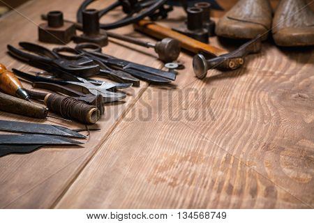 Set Of Tools For Shoemaker On Wooden Background. Copy Space.