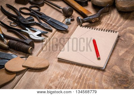 Set Of Tools, Notebook, Pencil For Shoemaker On A Wooden Background.