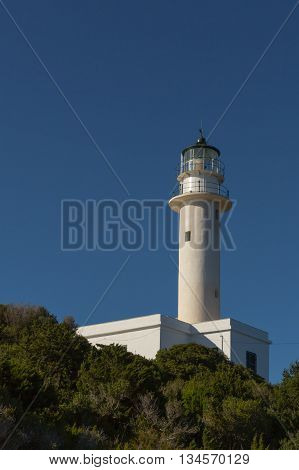 White lighthouse on a rock with blue sky