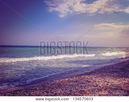 Beautiful sea with blue summer wave and ship on horizon. Summer sea background in violet tones. Tropical sea. Summer sea and beach. Endless sea. Daylight sea. Tropic ocean. Turquoise sea. Toned image.