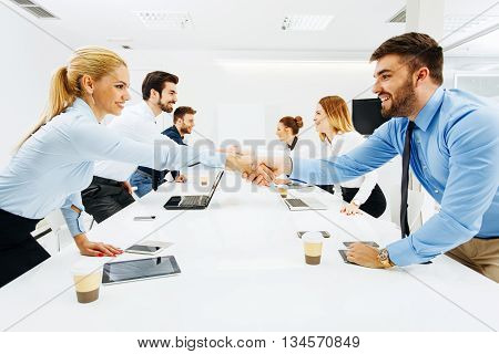 Young business people shaking hands after a successful agreement