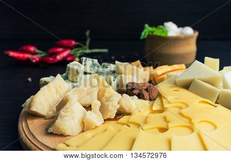 Cheese plate: Parmesan cheddar gouda blue cheese mozzarella and other with chili pepper and almonds on wooden board. Tasty appetizers. Cheese platter. Cheese board. Cheese slice. Selective focus.