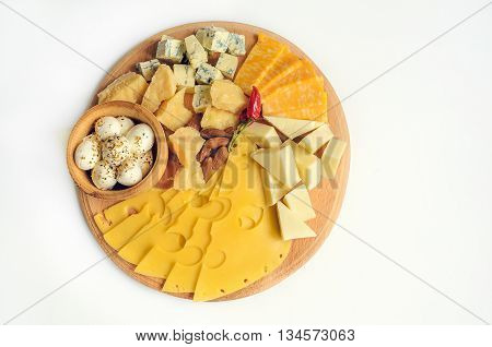 Cheese plate: Parmesan gouda blue cheese mozzarella and other with chili pepper and almonds on wooden board. Tasty appetizers. Cheese platter. Cheese board. Cheese slice. Isolated. Top view.