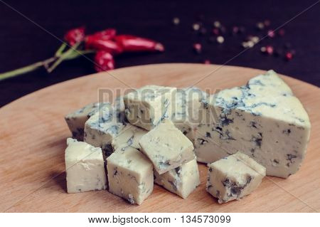 Blue cheese on wooden board. Blue cheese dressing. Bleu cheese. Tasty appetizer. Plate of cheese on wooden plate. Cheese platter. Cheese board. Cheese slice. Selective focus.