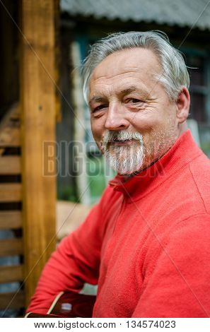 Close-up portrait of a handsome senior man in bright sweater looking at the camera and plays acoustic guitar outdoor. Smiling happy senior man with gray hair and beard. Outdoors. Vertical image.