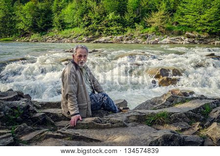 Senior man is sitting and thinking near the waterfall in the beautiful place. Looking far away. Serious senior man with gray hair and beard. Horizontal image.
