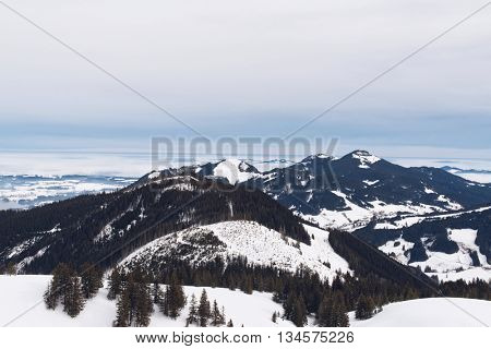 View from highest point of ski hill on rugged alpine forests and mountains under gray storm clouds