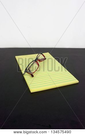 yellow legal pad on a black table with glasses