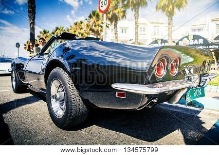 Benalmadena, Spain - June 21, 2015: A black Chevrolet Corvette C3, back view, parked in the port of Benalmadena (Spain), on June 21, 2015.