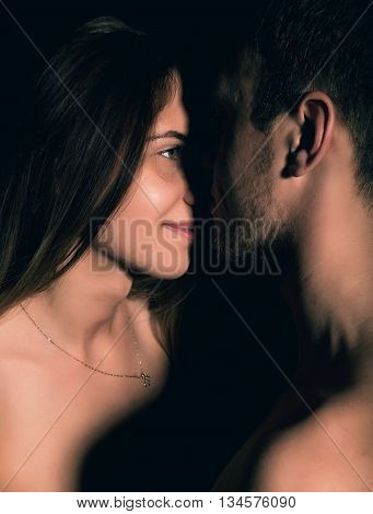 Close-Up Beautiful sexy young couple, naked man and woman on black background.