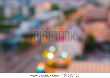 Blurred busy street view in the evening light showing colorful bokeh of traffic and street lights good for background