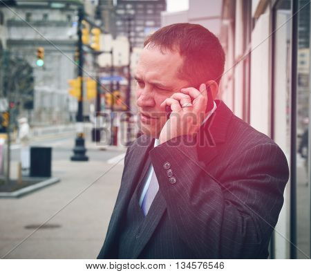 A business man is holding a phone with a red glow to conceptualize fear or stress. Use it for a career or problem message