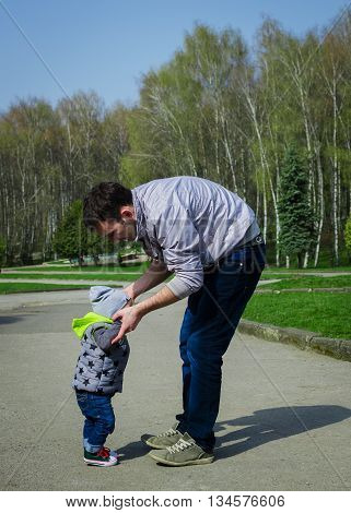 Father helping his son for the first steps. Baby boy taking first steps with father help in spring park. Walking toddler. Father's Day. Happy Fathers Day. Happy family. Father and baby.