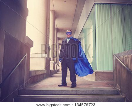 A business man is wearing a super hero blue costume with a suit in a city for a career success or innovation concept.