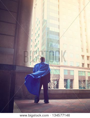 A business man wearing a super cape is standing in a city for a success strength or power career concept.