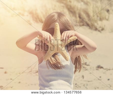 A little child is holding a starfish at a beach with sand for a travel vacation or explorer concept.