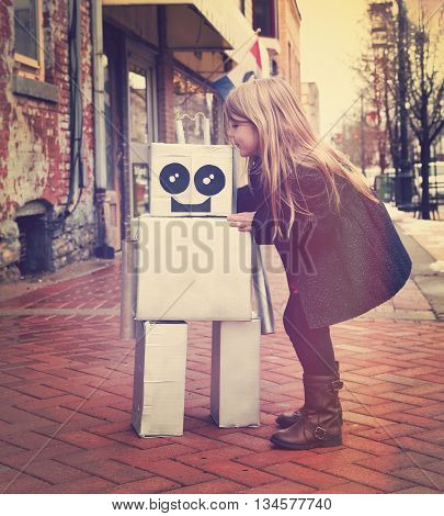 A little girl is hugging a metal cardboard robot downtown against a brick wall outside for a friendship or inventor concept.