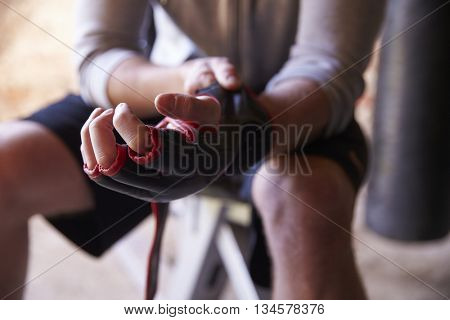Close Up Of Male Boxer Putting On Gloves In Gym