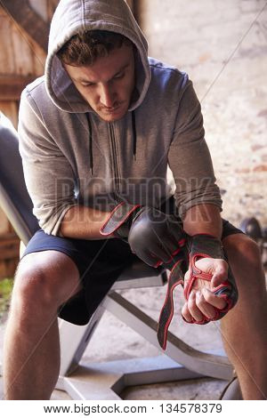 Male Boxer Putting On Gloves In Gym