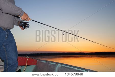 Spinning reel being worked at last light on a lake in Saskatchewan Canada