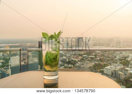 Mojito cocktail on table in rooftop bar. Rooftop bar in Bangkok Thailand. Rooftop bar with sunset.