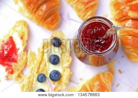 A jar of fresh raspberry jam on light rustic background close up in the garden selective focus