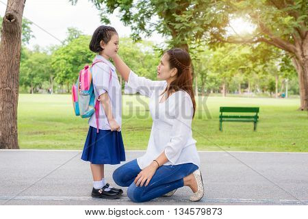 Back to school. Happy Asian mother with kids student in school. Asian mother adjusting kids student shirt in school.