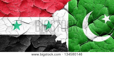 Syria flag with Pakistan flag on a grunge cracked wall
