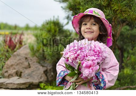 The little girl close in a pink hat and a raincoat. green background. Sweet toddler girl with pink flowers